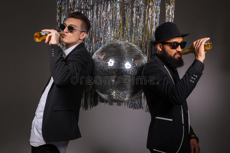 Two confident men standing near disco ball and drinking beer stock photos