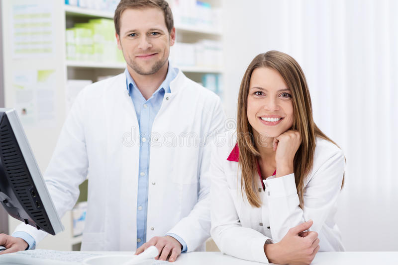 Two confident pharmacists at work. Two confident young pharmacists at work with the men working on the computer as the women leans forwards royalty free stock image