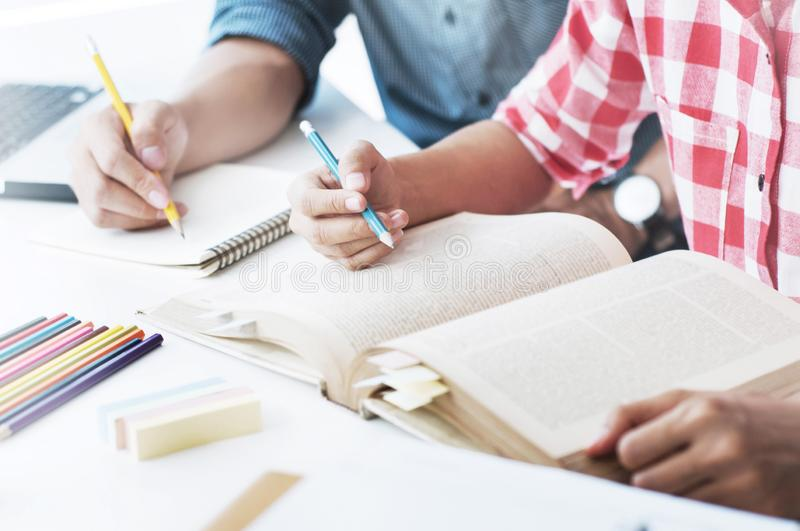 Two confident students reading a book or doing homework together while sitting at the home royalty free stock photography