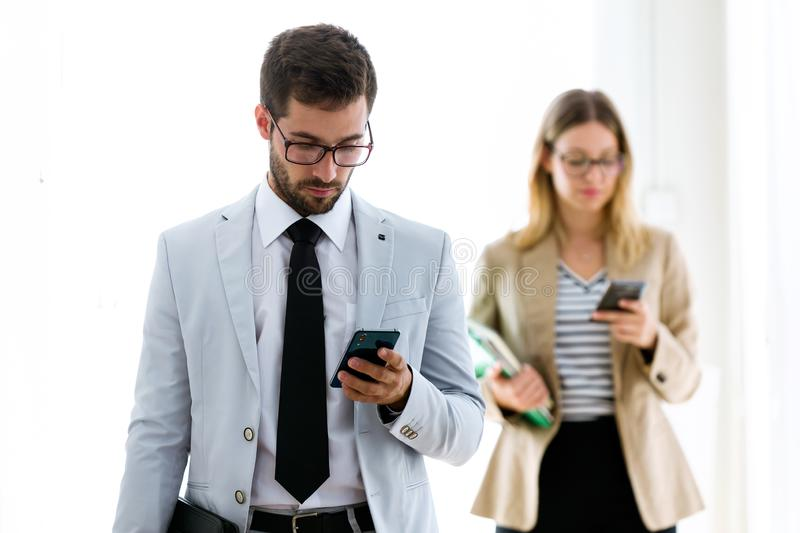 Two confident young business partners texting with their smartphones in a hallway of they company. royalty free stock photos