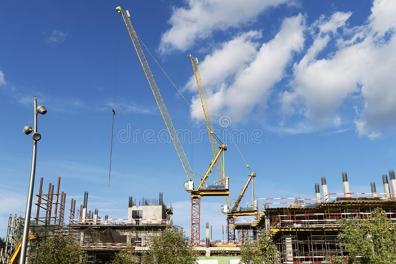 Two construction cranes on a building construction. High crane on a blue sky with clouds. The construction of a multi-storey. Building royalty free stock image
