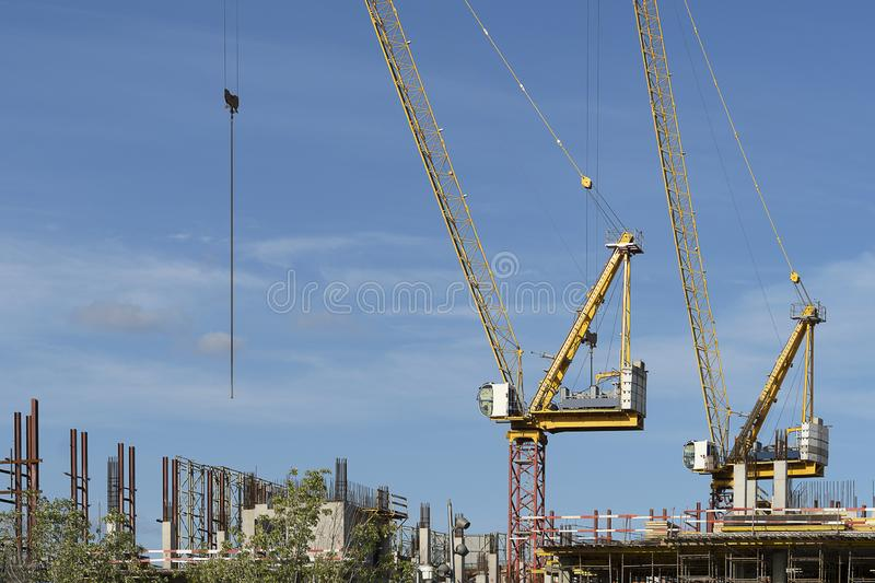 Two construction cranes at a construction site. Tall crane on a blue sky. The construction of a multi-storey royalty free stock photo