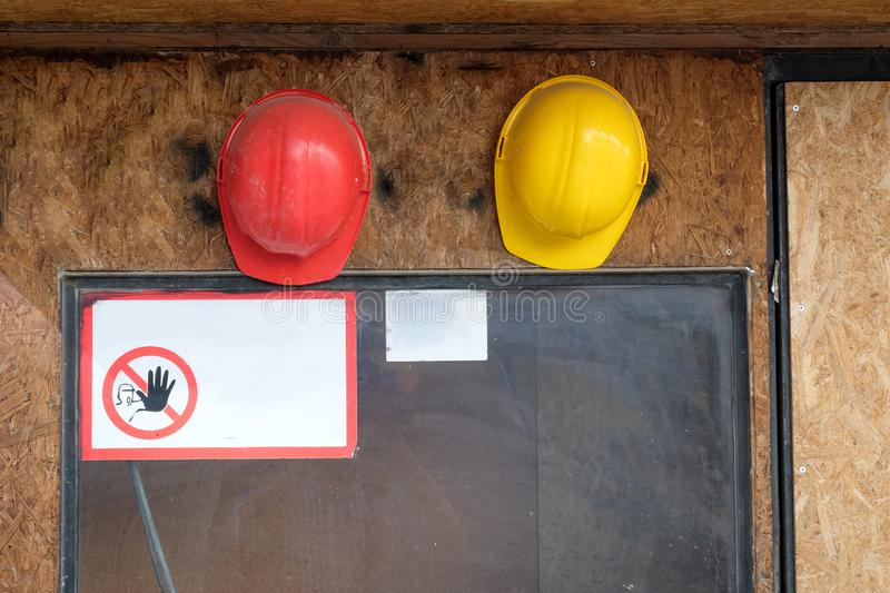 Two construction hard hats on the wall with warning sign royalty free stock images