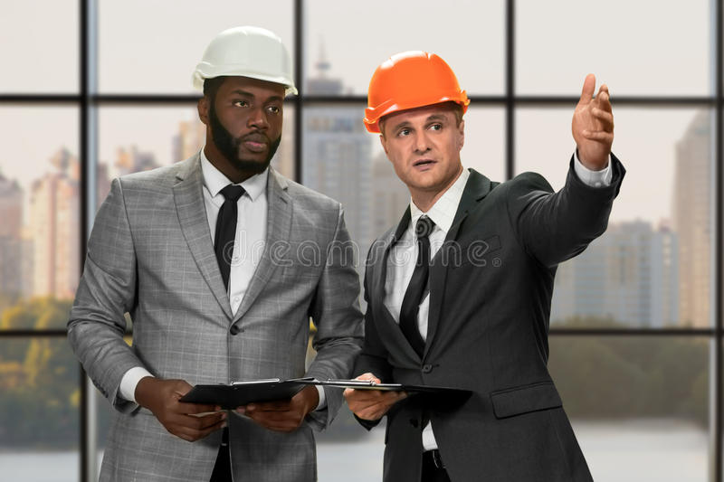 Two construction managers' daytime conversation. Construction managers in big city. Re-building an entire district. This is way too expensive royalty free stock photo