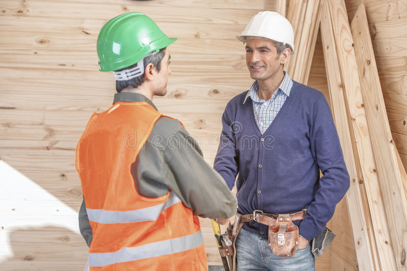 Two Construction Professionals. Shaking Hands at the jobsite stock image