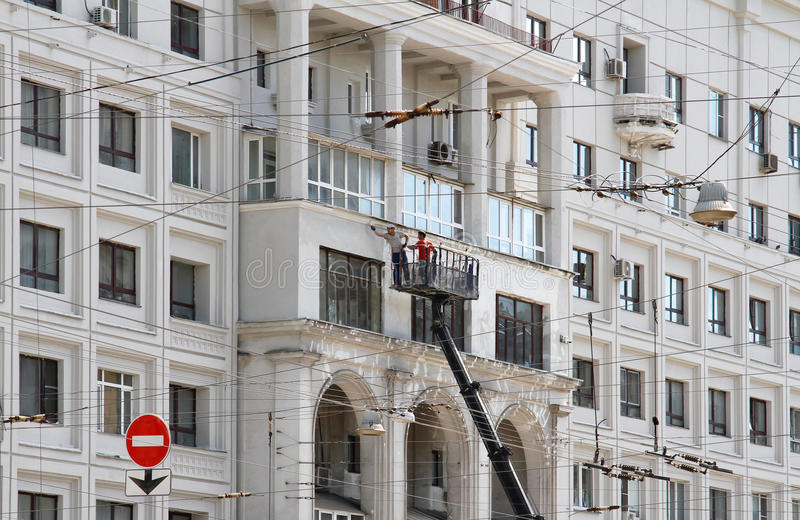 Two construction workers in bucket of crane vehicle are reconstructing the facade of building in Moscow royalty free stock images