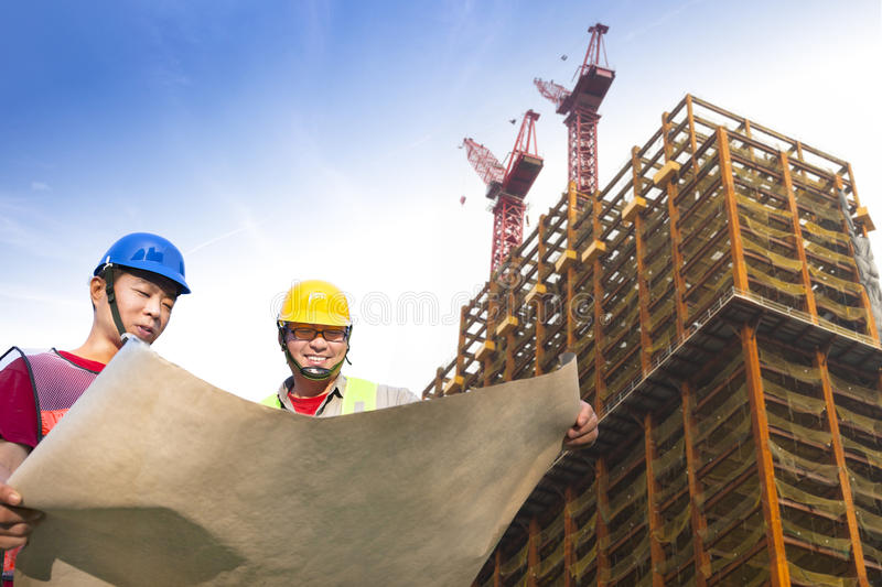 Two construction workers with building. Two construction workers with giant cranes and building stock image