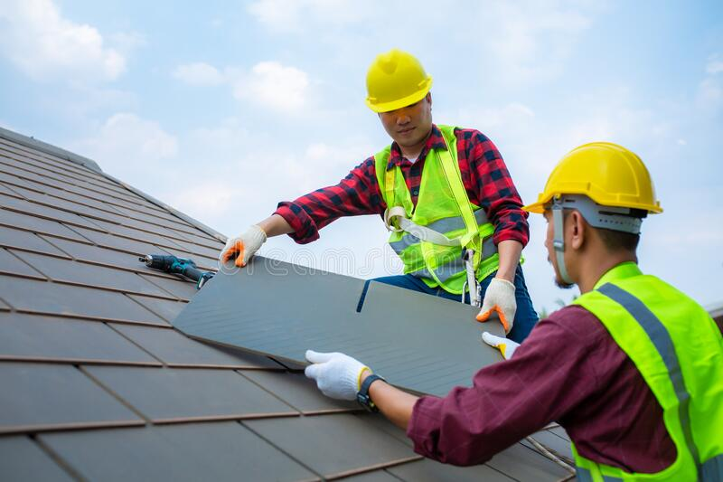 Two construction workers helped to Fixing roof tiles, turning the gray in the house with the blue sky in the safety suit for stock photo