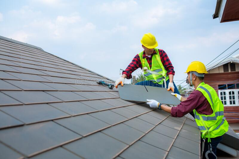 Two construction workers helped to Fixing roof tiles, turning the gray in the house with the blue sky in the safety suit for royalty free stock photography