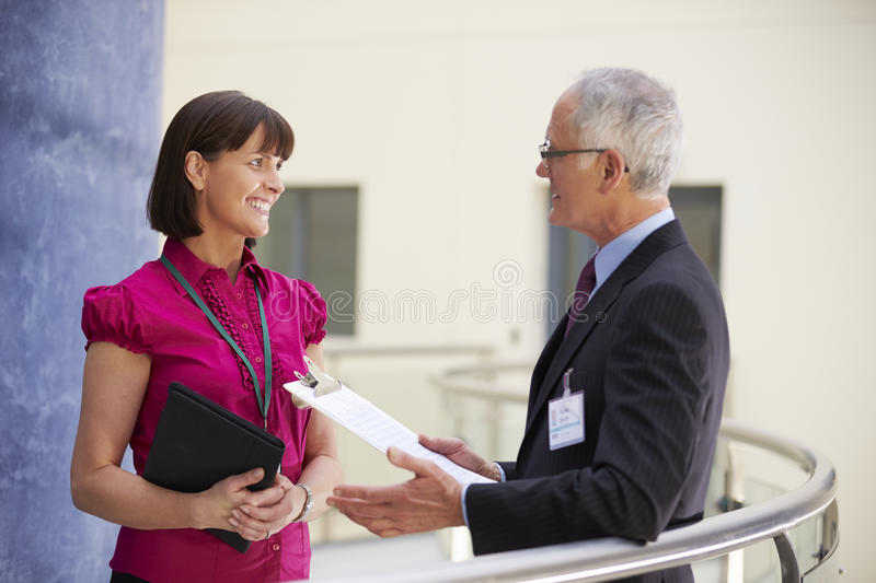 Two Consultants Meeting In Hospital Reception stock image