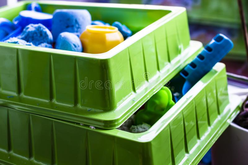 Two containers with kinetic sand and plastic toys for the development of fine motor skills and creative imagination in children. Close-up stock photo