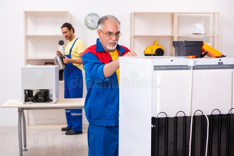 Two contractors repairing fridge at workshop royalty free stock photo