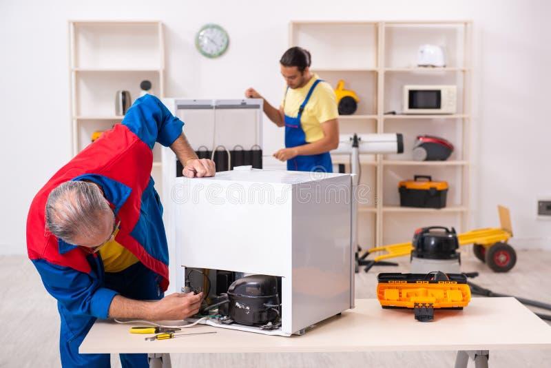 Two contractors repairing fridge at workshop royalty free stock image