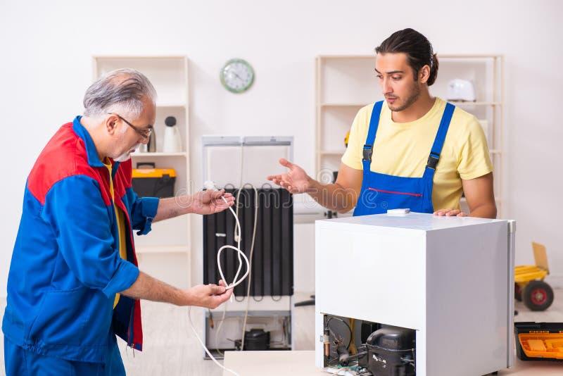 Two contractors repairing fridge at workshop royalty free stock photo