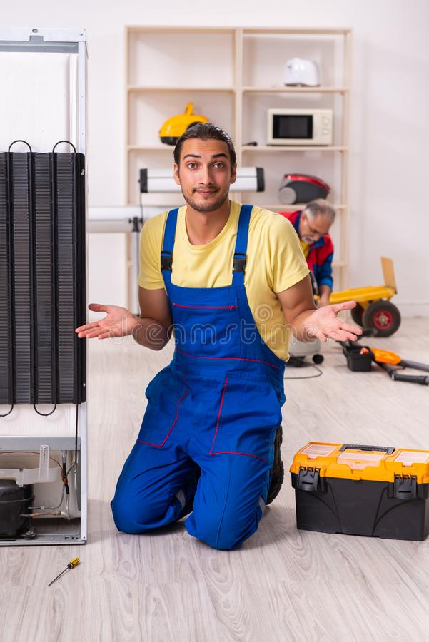 Two contractors repairing fridge at workshop stock photo