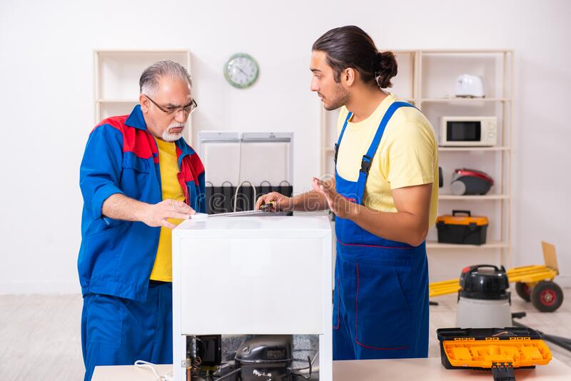 Two contractors repairing fridge at workshop royalty free stock photography