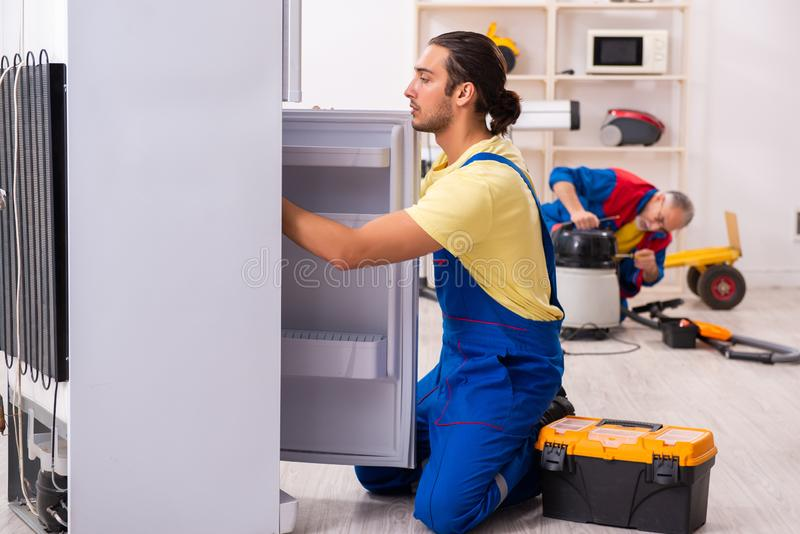 Two contractors repairing fridge at workshop royalty free stock photos