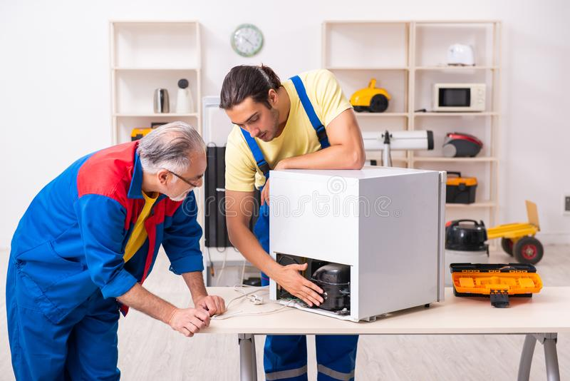 Two contractors repairing fridge at workshop stock photos