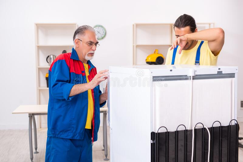 Two contractors repairing fridge at workshop royalty free stock images