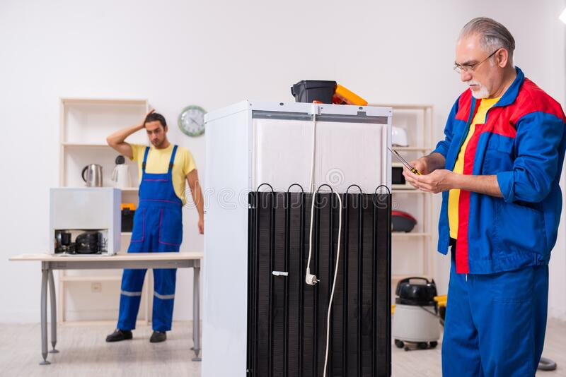 Two contractors repairing fridge at workshop stock images