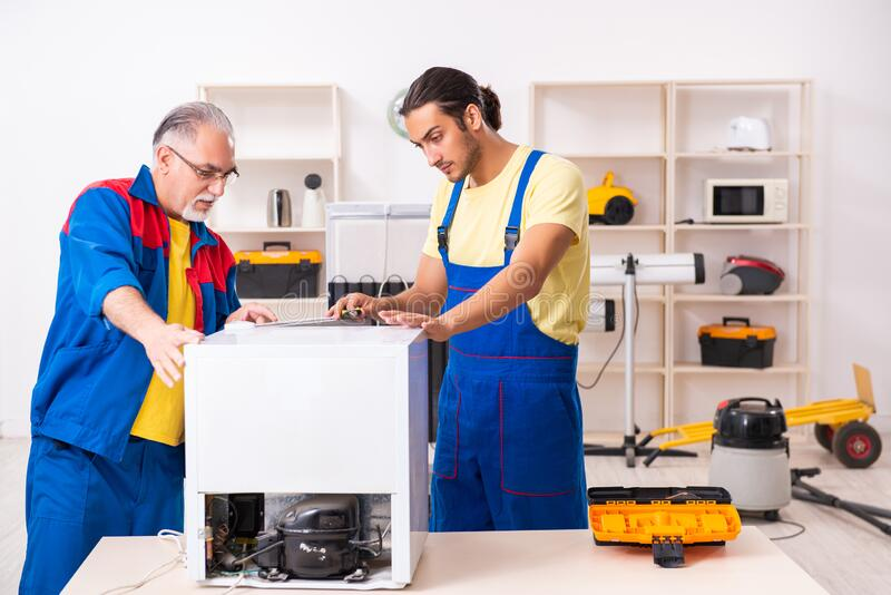 Two contractors repairing fridge at workshop royalty free stock photos