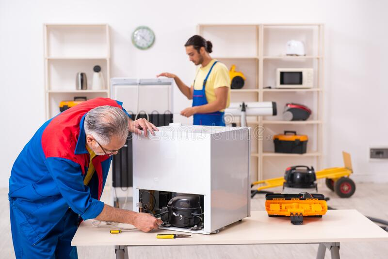 Two contractors repairing fridge at workshop stock image