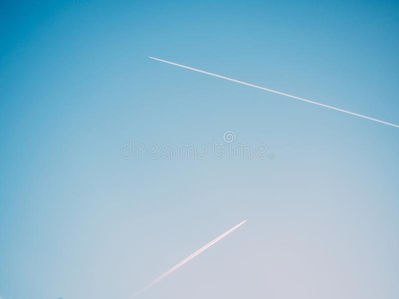 Two contrails in blue sky royalty free stock images