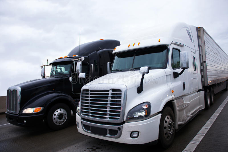 Two contrast modern semi truck different models black and white royalty free stock photo
