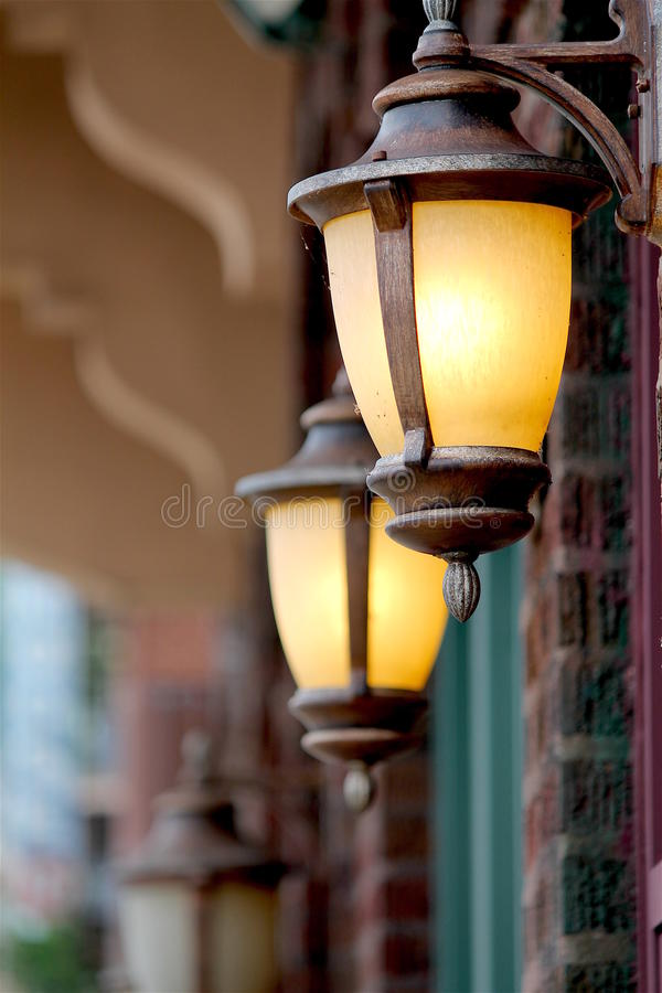 Two copper lanterns outside brick storefront in historical city royalty free stock photography