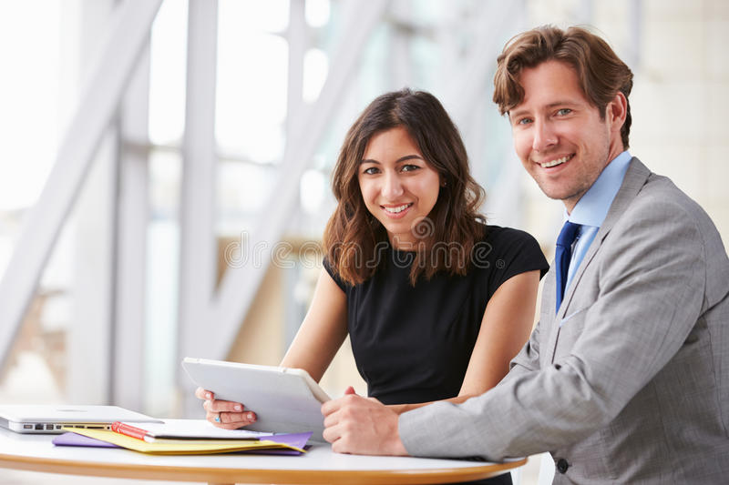 Two corporate business colleagues at work smiling to camera stock images