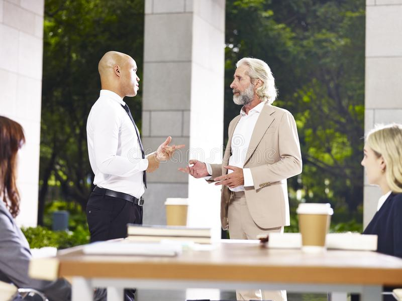 Two corporate executives debating during meeting. Caucasian and latino corporate business executives discussing debating during meeting royalty free stock photography
