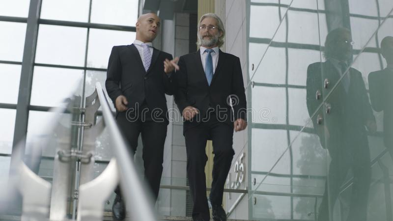 Two corporate executives talking while descending stairs stock image