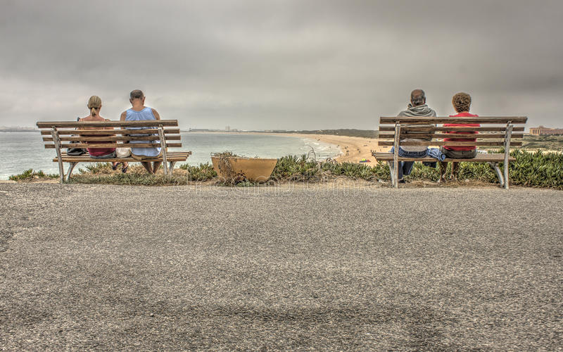 Two Couple Sitting on Bench Near Beach stock photography