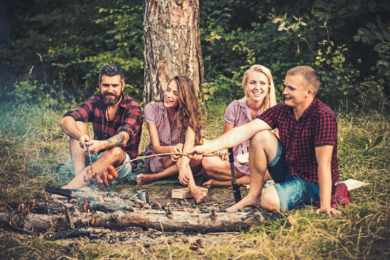 Two couples camping in woods. Guys frying sausages over fire. Smiling friends sitting around campfire in the evening stock photos