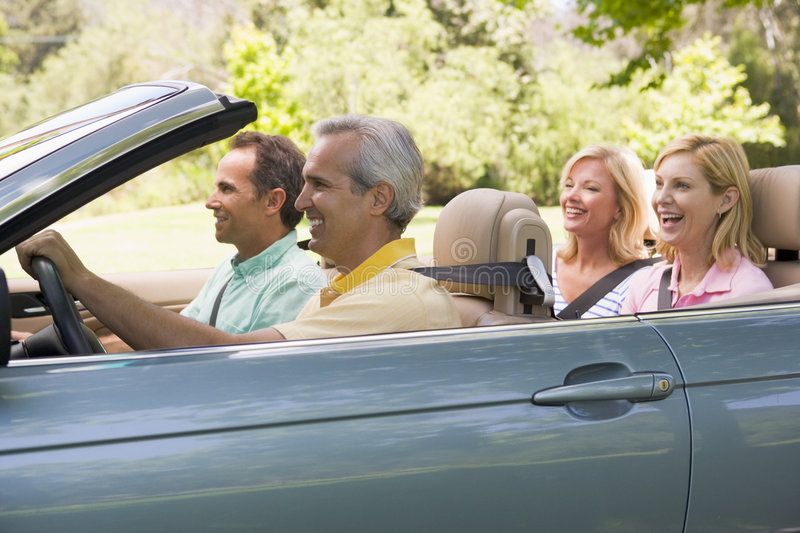 Two couples in convertible car smiling royalty free stock photography