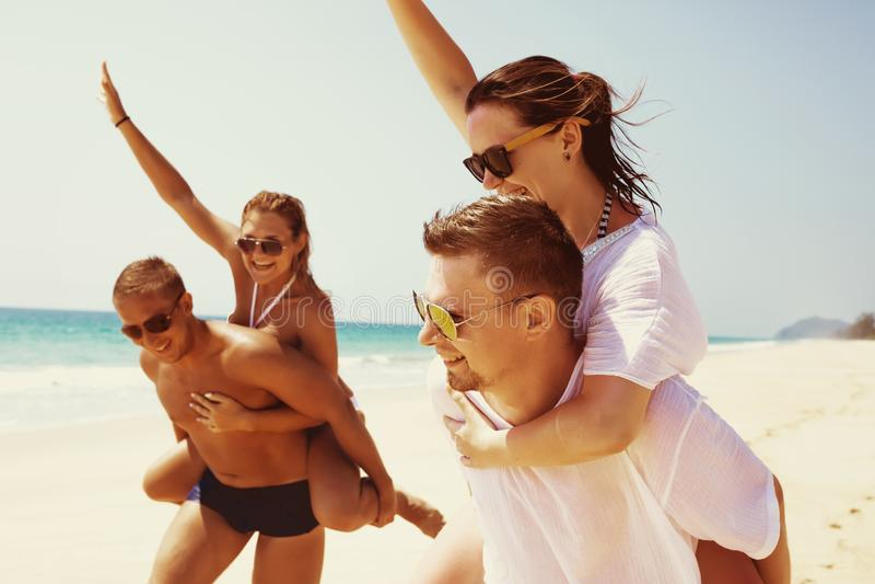 Two couples friends fun beach run royalty free stock photos