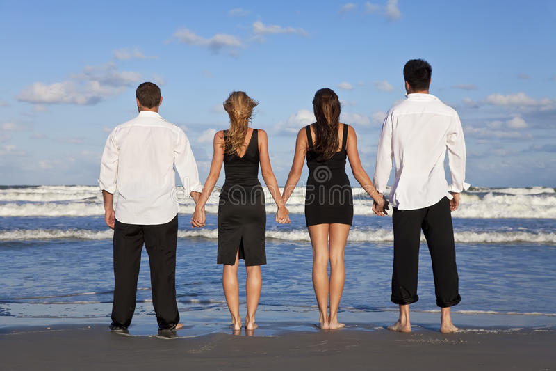 Two Couples, Holding Hands On A Beach. Four young people, two couples, holding hands, looking out to sea on a beach stock image