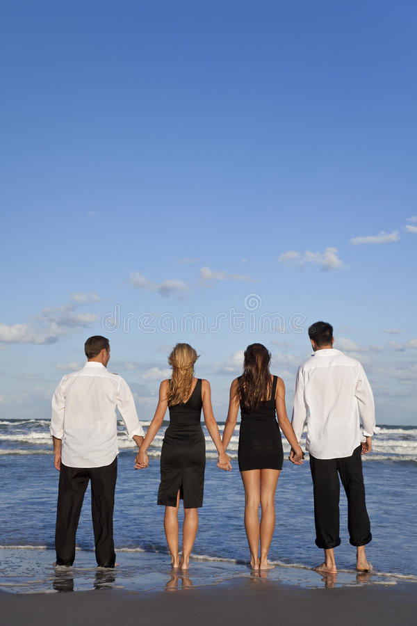 Two Couples, Holding Hands On A Beach royalty free stock photos