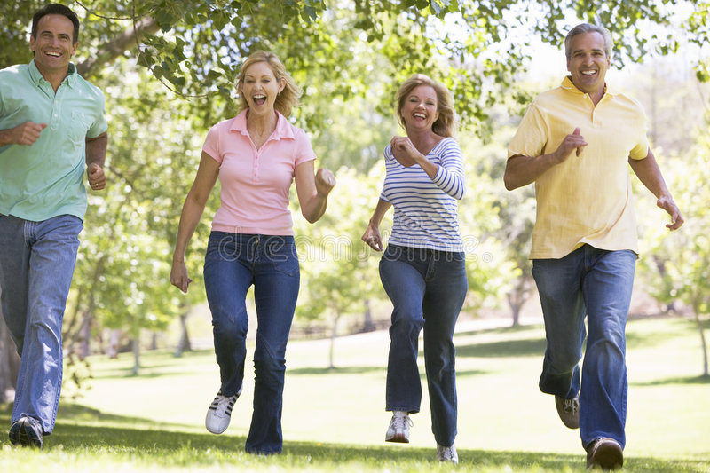Two Couples Running Outdoors Smiling Royalty Free Stock Image