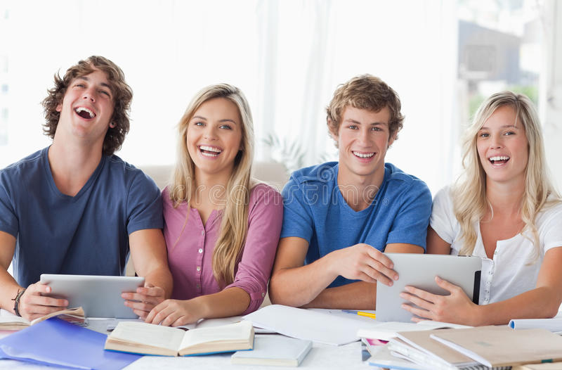 Two Couples Sit Together And Work With The Help Of Tablet Pc S Stock Images