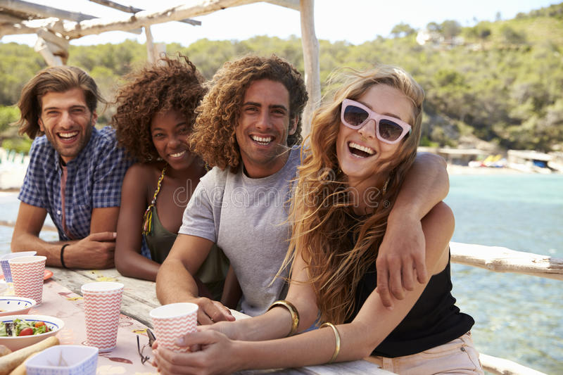 Two couples sitting at a table by the sea look at each other stock photography