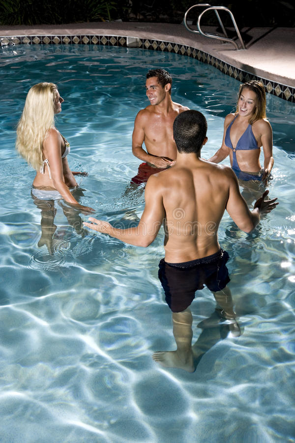 Two Couples In Swimming Pool At Night Royalty Free Stock Photography