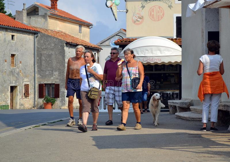Couples of tourist eat ice-cream on street. Two couples of tourist walking along a street of Premantura and eat ice-cream royalty free stock image