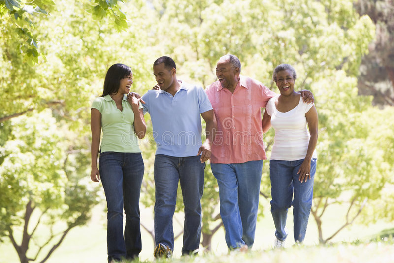 Two couples walking outdoors arm in arm smiling royalty free stock photo