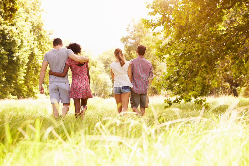 Two couples walking together in the countryside, back view stock images