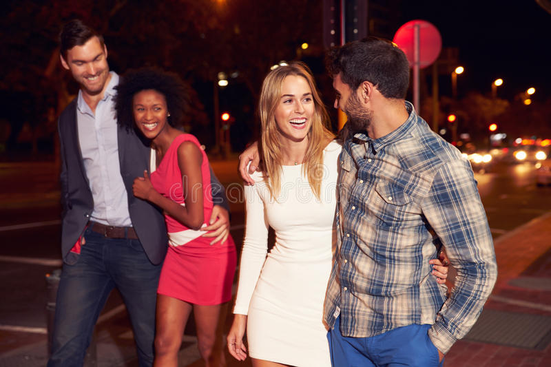 Two couples walking through town together at night stock photography