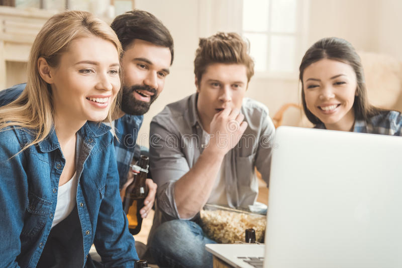 Two couples watching movie on laptop. Two young couples watching movie on laptop while drinking beer and eating popcorn royalty free stock image