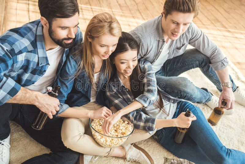 Two couples watching movie. Two young couples watching movie while drinking beer and eating popcorn stock photos