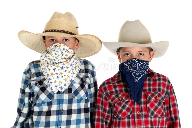 Download Two Cowboy Brothers Wearing Hats And Bandanas Looking At Camera Stock Photo