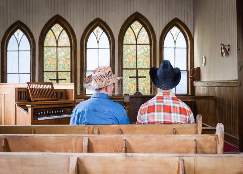 Two cowboys sitting together in a church pew. Horizontal image of two caucasian cowboys sitting in an old romantic church pew in front of a wall of arched stock photo